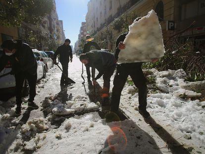 Vecinos retiraban con palas el hielo de la calzada en el barrio madrileño de Retiro el pasado día 12.
