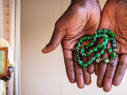 Assane Seck sostiene el retrato de su esposa Marie Ba fallecida por covid en Dakar (Senegal) y su 'tasbih', un rosario musulmán.