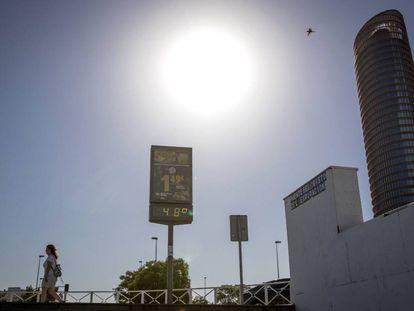 Una mujer pasa junto a un termómetro que marca 48º al sol frente a Torre Sevilla, el pasado 18 de junio.