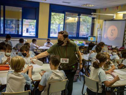 Una maestra dispensa gel desinfectante a los alumnos en el colegio Maestro Padilla de Madrid, este martes.