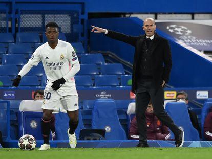 Zidane da órdenes desde la banda mientras Vinicius conduce el balón.