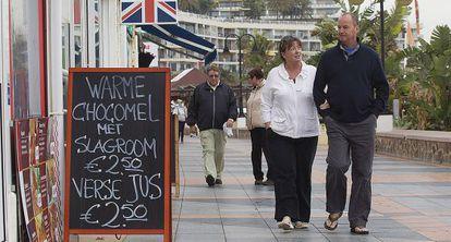 Dos turistas caminan por el paseo marítimo de Torremolinos.
