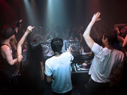 Varios DJ animan al público en una discoteca  a hacer olas.
