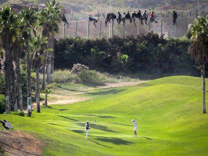 Una docena de inmigrantes permanece encaramado a la valla de Melilla mientras dos personas juegan al golf.