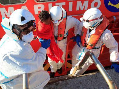 Los efectivos de rescate trasladan a un niño localizado en una patera.
