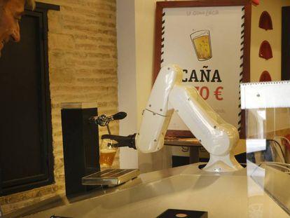 Un cliente pide una caña al camarero robotizado de Macco, en La Gitana Loca, en Sevilla.