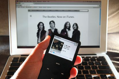 Un usuario utiliza su iPod para reproducir una canción de los Beatles tras descargársela de la tienda digital  iTunes.