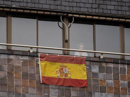 Una vecina de Carabanchel se asoma el pasado viernes a la ventana, en la que ha colocado una bandera de España.
