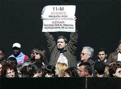 Una de las víctimas exige responsabilidades criminales a Acebes y Aznar en una pancarta.