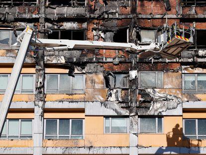 Dos bomberos trabajan en una grúa ante las viviendas incendiadas.