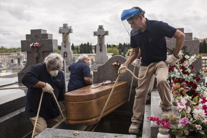 Enterradores bajan el ataúd de una fallecida por coronavirus a los 94 años en una residencia de ancianos, en el cementerio de la Almudena, Madrid, el 7 de abril de 2020.