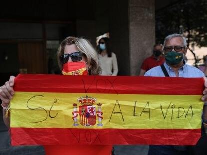Una mujer sostiene una bandera de España con un mensaje en contra de la eutanasia frente al Tribunal Constitucional el 16 de junio de 2021, en Madrid.