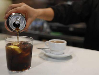 Una camarera sirve un refresco de cola. En vídeo, posibles medidas para reducir el consumo de bebidas azucaradas.