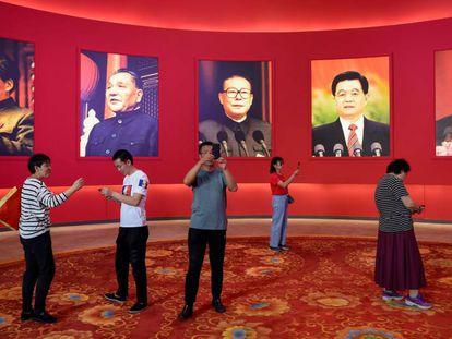 Un grupo de personas fotografía una exposición por el 70º aniversario de la República Popular de China con los retratos (de izquierda a derecha) de Mao Zedong, Deng Xiaoping, Jiang Zemin, Hu Jintao y el presidente actual, Xi Jinping, ayer en Pekín.