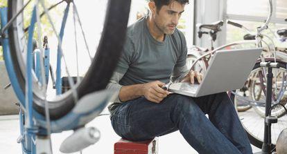 Hombre usando una computadora portátil en la tienda de bicicletas