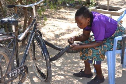 Una de las mujeres de Msitu Wa Tembo vigilan y reparan las bicicletas del negocio de alquiler, que se ha convertido en una reseñable forma de ingresos para su comunidad.