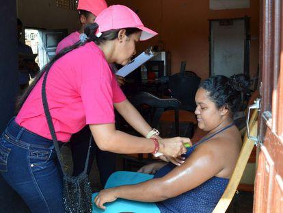 Personal sanitario enseña a una mujer embarazada cómo echarse repelente contra el virus del zika en Barranquilla (Colombia)