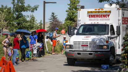An emergency vehicle next to the queue of people waiting to enter a water park and beat the heat, in Calgary, Canada.