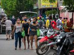 People wearing face masks walk in the port zone of the city of Breves, southwest of the Marajo Island, an island at the mouth of the Amazon River in the Brazilian state of Para, on May 30, 2020, amid the COVID-19 coronavirus pandemic. - The pandemic has killed at least 364,362 people worldwide since it surfaced in China late last year, according to an AFP tally at 1100 GMT on Saturday, based on official sources. (Photo by TARSO SARRAF / AFP)