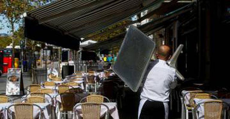 Un camarero recoge una mesa de una terraza de un restaurante del barrio de la Barceloneta de Barcelona.