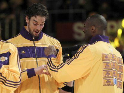 Los jugadores de Lakers Pau Gasol y Kobe Bryant miran sus anillos de campeones de la NBA durante la ceremonia de entrega en octubre de 2010.