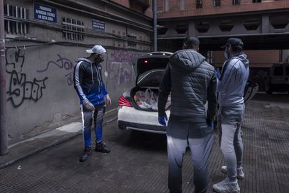 Omar Montes y sus dos colegas, preparados para sacar los alimentos del coche.