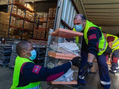 Operarios de los talleres municipales del Ayuntamiento de Barcelona trabajan en el almacén donde se guarda el material electoral del 14-F.