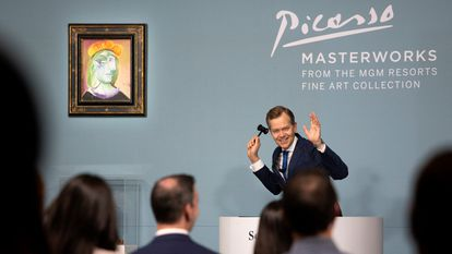 """Oliver Barker, auctioneer and chairman of Sotheby's Europe, declares the sale of Pablo Picasso's """"Femme au béret rouge-orange,"""" displayed at left, during an auction at the Bellagio hotel and casino Saturday, Oct. 23, 2021, in Las Vegas. Sotheby's and the MGM Resorts Fine Art Collection hosted the auction, which raised $109 million from eleven pieces. (AP Photo/Ellen Schmidt)"""