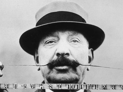 Retrato de un hombre que mide la longitud de su bigote con una cinta métrica en 1905.
