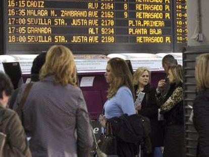 Varias personas esperan en la estación de Atocha, en Madrid, ante un panel que informa del retraso de los trenes.