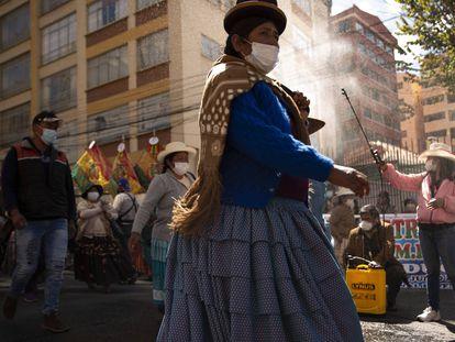 Una mujer rocía desinfectante a manifestantes en medio de la pandemia COVID-19, durante una marcha pidiendo acceso gratuito a internet y computadoras al gobierno, para que sus hijos puedan tomar clases en línea, en La Paz, Bolivia.