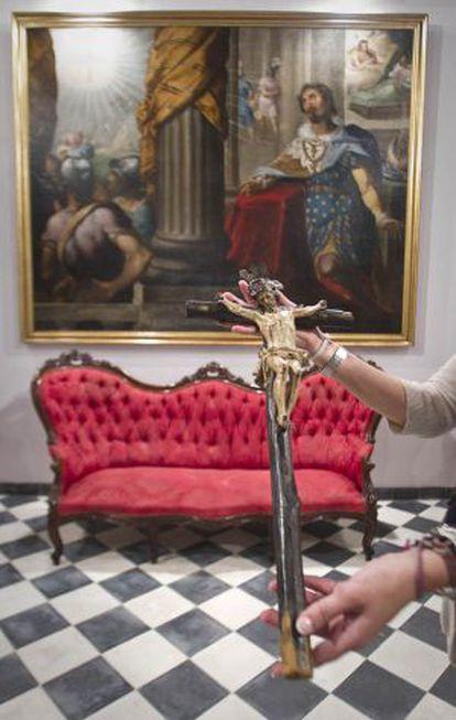 La cruz de los ajusticiados delante del lienzo de Herrera el Viejo en la sala de Cabildos.