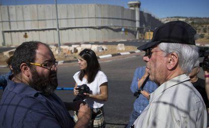 Vargas Llosa (d), junto a Yehuda Shaul ( Breaking the Silence), a la salida de Jerusalén, con el muro divisorio de fondo