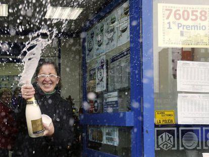 Una mujer descorcha una botella de champán en la administración número 12 de Alcalá de Henares, donde se han vendido 130 series del 76.058