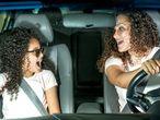Madre e hija cantan en el coche.