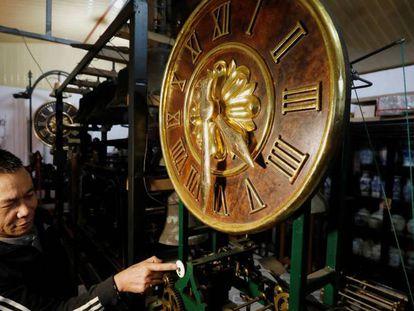 El coleccionista de relojes Pham Van Thuoc, con uno de los aparatos restaurados en su taller de Vietnam.