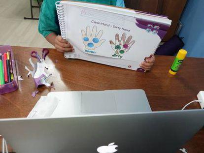 Un niño muestra un trabajo a su maestra a través de una videollamada.