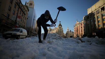 Una persona, con su coche a la izquierda averiado, intenta romper hielo con una pala, en la calle Alcalá.