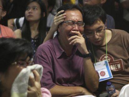 Familiares de los pasajeros del avión de AirAsia reciben la noticia de que se han encontrado cadáveres en el mar de Java.