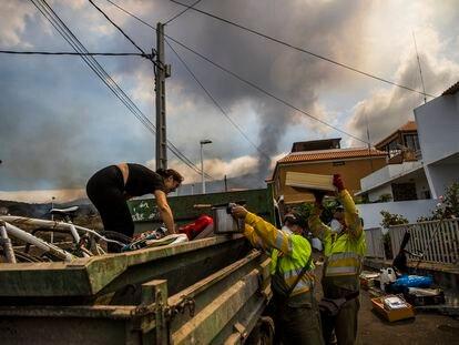 Vecinos del barrio de Todoque, ayudados por empleados municipales de Los Llanos, recogen sus pertenencias para ser evacuados por la cercanía de la lava.