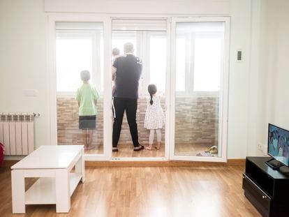 Djamel Zatout, junto a sus hijos en el balcón acristalado de la nueva vivienda ofrecida por el ayuntamiento a la familia.