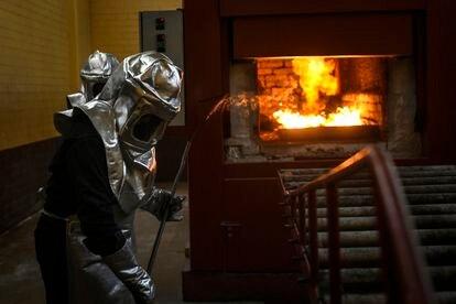 Dos trabajadores de un panteón en Estado de México creman los restos de una persona.