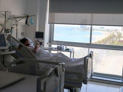 Un paciente con covid mira el móvil desde una habitación del Hospital del Mar de Barcelona, donde está ingresado