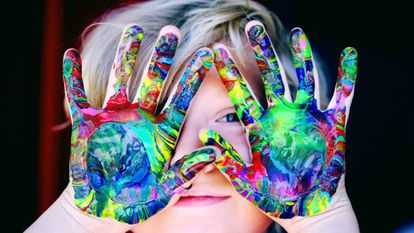 Un niño muestra sus manos pintadas.