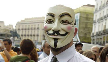 Un manifestante en la plaza del Sol de Madrid con una careta de Anonymous.