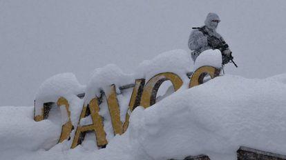 Un oficial de policía suizo armado hace guardia en el techo de un hotel cerca del bloque donde tiene lugar la reunión anual del Foro Económico Mundial en Davos (Suiza).