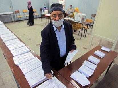 Un votante recoge las papeletas de las listas de candidatos, este sábado en un colegio electoral de Argel.
