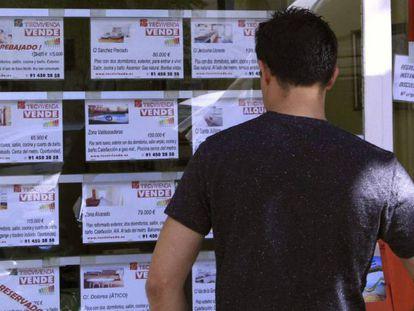 Un joven mira los anuncios de pisos en venta en el escaparate de una inmobiliaria, en Madrid.