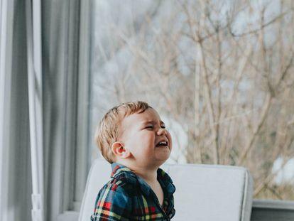 Un niños llora en el salón de su casa.