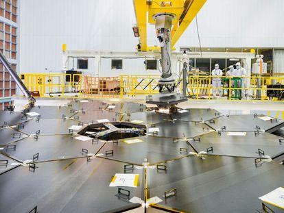 Montaje del último segmento de los 18 que componen el espejo principal del futuro telescopio espacial 'James Webb', en la enorme sala limpia donde se está ensamblando el observatorio en el Centro de Vuelos Espaciales Goddard, de la NASA, en Greenbelt (Maryland, EE UU).